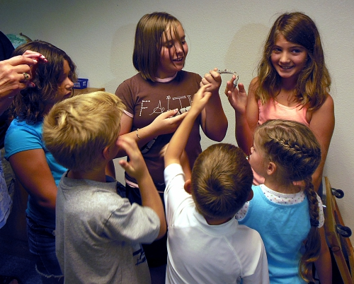 Kids handling a friendly snake at a Summer Reading Program.